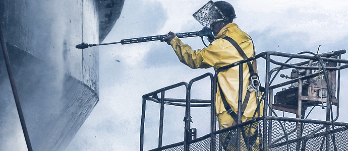 oil rig worker using a pressure washer